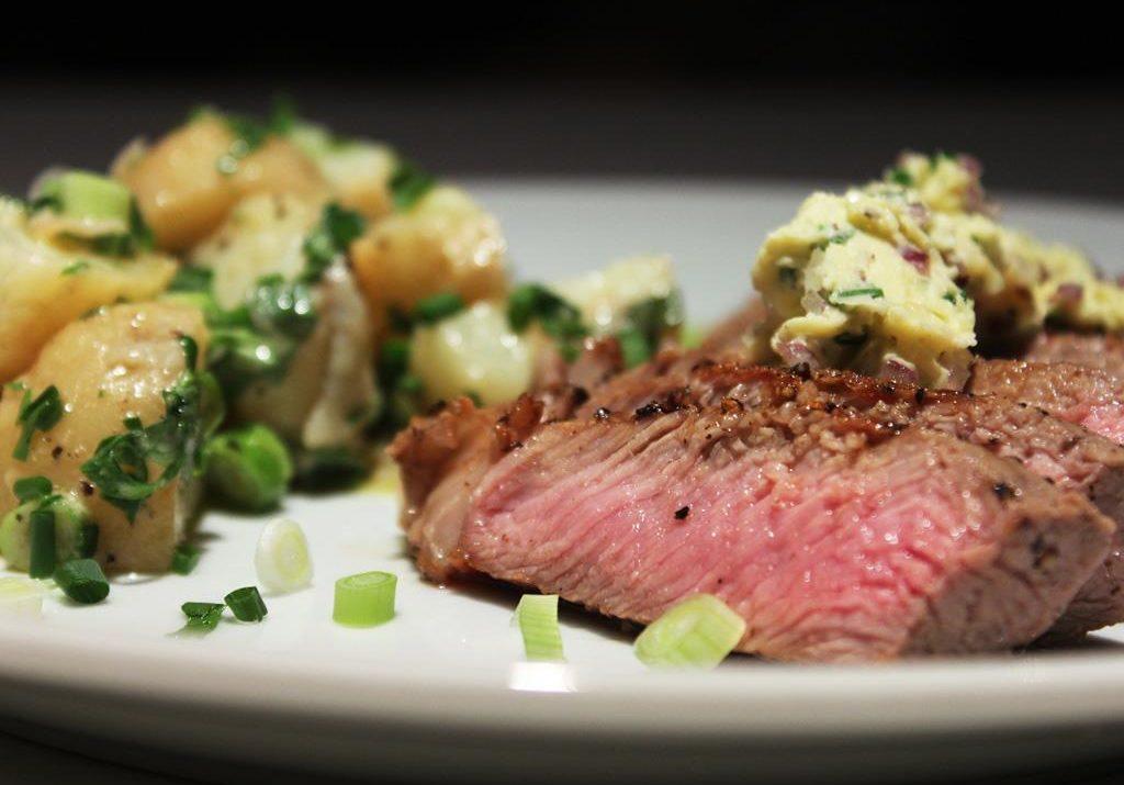 Steaks grillés avec beurre à l'ail et à la ciboulette et salade de pommes de terre à la française